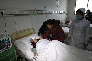 A girl stabbed in the Guangshan attack lies in her hospital bed two days after the incident on Dec. 16, 2012.