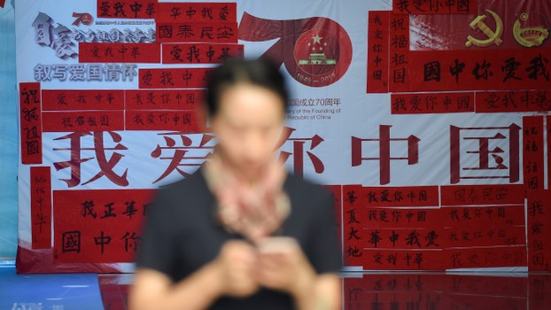 A woman uses her mobile phone in front of a billboard displaying best wishes for the 70th anniversary of the founding of the People's Republic of China in Beijing, Sept. 25, 2019.