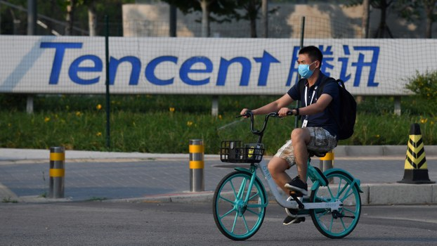 A man walks past a sign for Tencent, the parent company of Chinese messaging app WeChat, outside the Tencent headquarters in Beijing, Aug. 7, 2020.