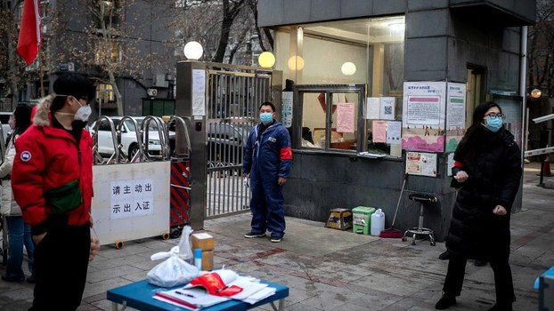Security officers and residents wearing facemasks to protect against the COVID-19 coronavirus stand at the entrance of a residential compound in the Chinese capital Beijing, Feb.