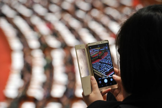 A journalist uses a smartphone to photograph deputies attending the second plenary meeting of the Fourth Session of the 12th National People's Congress at the Great Hall of the People in Beijing, March 9, 2016.