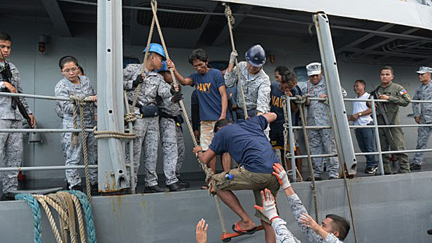 Rescued Filipino fishermen transfer to a Philippine Coast Guard ship as they head back to the central province of Occidental Mindoro, June 14, 2019.