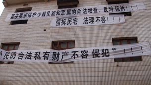In an undated photo provided by a local resident, property owners in Changsha post banners protesting another forced eviction. Credit: Local resident