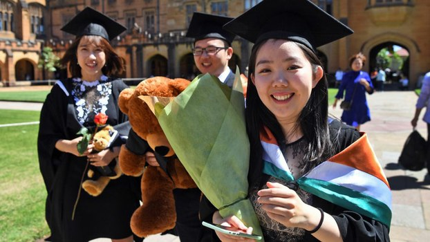 Students from China pose for family photos after graduating from a course in commerce at Sydney University, Oct. 12, 2017.