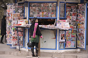 A woman looks at newspapers and magazines on one of Beijing's many newsstands, Dec. 3, 2008.