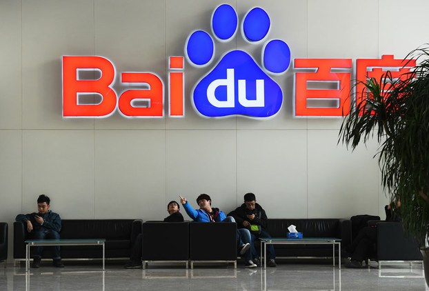 People sitting below the logo of Chinese search giant Baidu at the firm's headquarters in Beijing, in file photo.