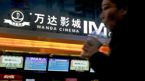 A Chinese moviegoer walks into the Wanda Cinema at the Wanda Group building in Beijing, Jan. 12, 2016.
