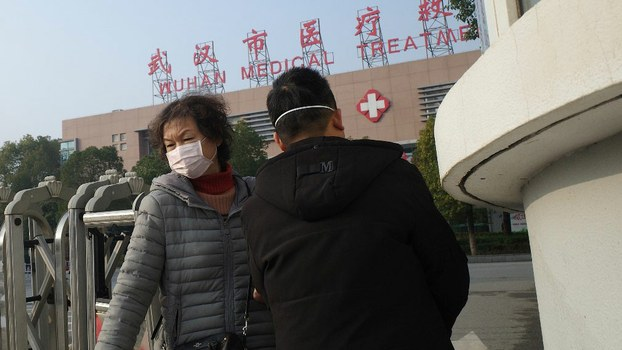 A woman (L) leaves the Wuhan Medical Treatment Center, where a man who died from a respiratory illness was confined, in the central Chinese city of Wuhan, Hubei province, Jan. 12, 2020.