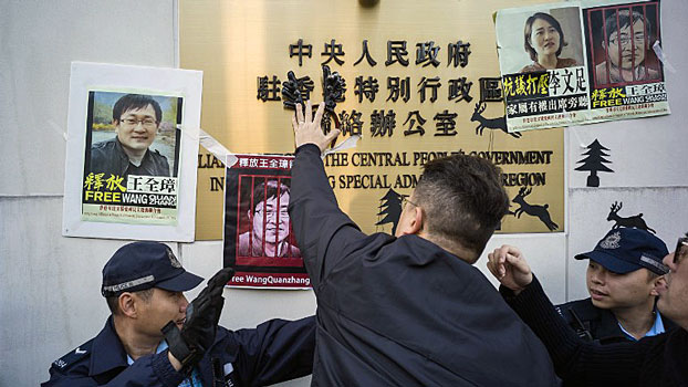 Activists tape posters of detained Chinese human rights lawyer Wang Quanzhang and his wife Li Wenzhu to signage during a rally outside the Chinese Liaison Office in Hong Kong, Dec. 26, 2018, as Wang's trial is set to begin in China.