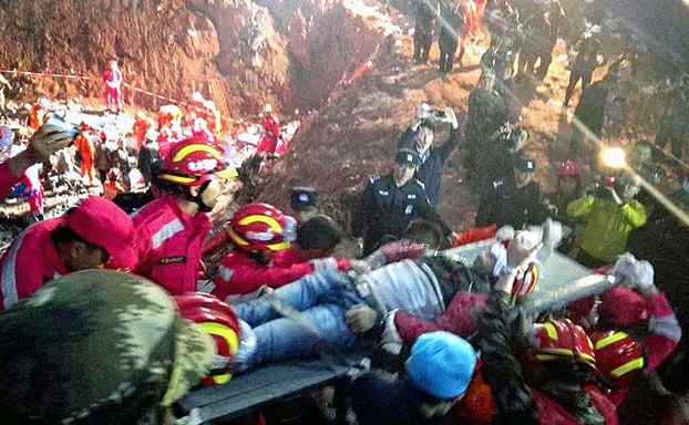 Chinese rescuers carry Tian Zeming after pulling him out of debris from a mudslide in Shenzhen, southeastern China's Guangdong province, Dec. 23, 2015.
