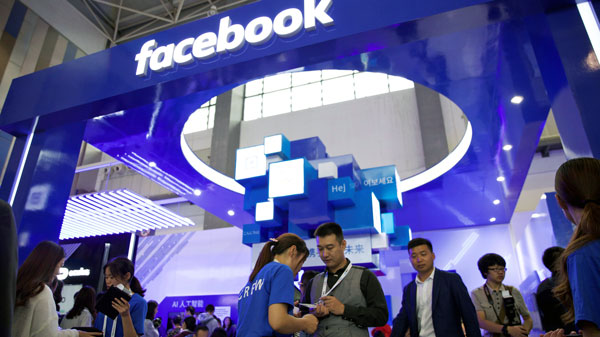 People stand near a Facebook booth at the China International Big Data Industry Expo in Guiyang, southwestern China's Guizhou province, May 27, 2018.