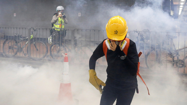 A protester shields himself from tear gas during a confrontation with police in Tai Wai, Hong Kong, Aug. 10, 2019.