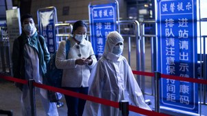 Passengers wear hazmat suit as they arrive at the Wuhan Wuchang Railway Station in Wuhan, to leave the city in China's central Hubei province, early April 8, 2020.