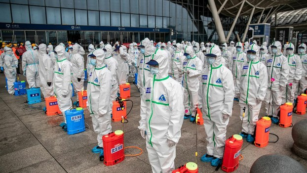 Staff members line up at attention as they prepare to spray disinfectant at Wuhan Railway Station in China's central Hubei province, March 24, 2020.