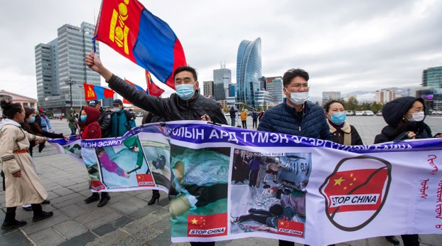 Protesters hold banners and wave the Mongolian flag in Ulaanbaataar, capital of Mongolia, to oppose Chinese policies in Inner Mongolia, Oct. 1, 2020.