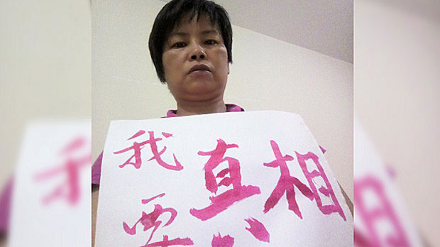 Zhang Wuzhou, sister of rights activist Zhang Liumao who died in jail, holds a placard saying 'We want the truth.'