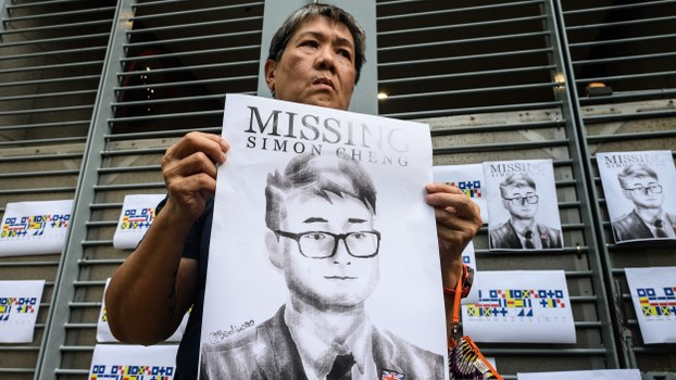 An activist holds an illustration of Simon Cheng during a gathering outside the British Consulate-General building in Hong Kong, Aug. 21, 2019.