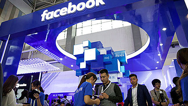 People stand near a Facebook booth at the China International Big Data Industry Expo in Guiyang, Guizhou province, China, May 27, 2018.