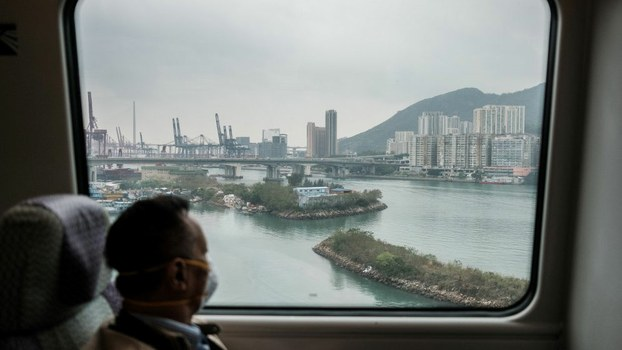 A passenger wears a face mask as a precautionary measure against the COVID-19 coronavirus as he travels on the city-linked train to Hong Kong's international airport, March 19, 2020.