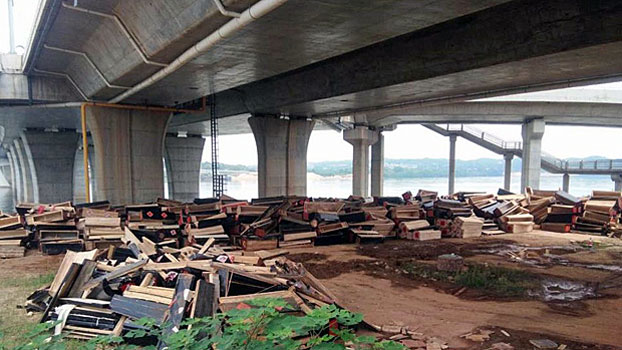 Destroyed wooden coffins sit under a bridge in Anfu county, southeast China's Jiangxi province, Aug. 5, 2018.