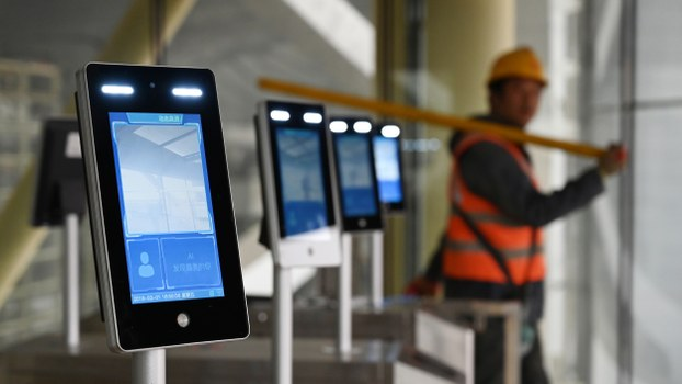 A construction worker walks past facial recognition screens at the entrance to the terminal building of the new Beijing Daxing International Airport, in Beijing, March 1, 2019.