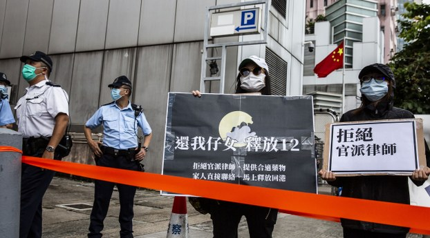 Family members of some of the 12 Hong Kong residents detained in mainland China after trying to flee to Taiwan protest outside China's Liaison Office in Hong Kong, Sept. 30, 2020.