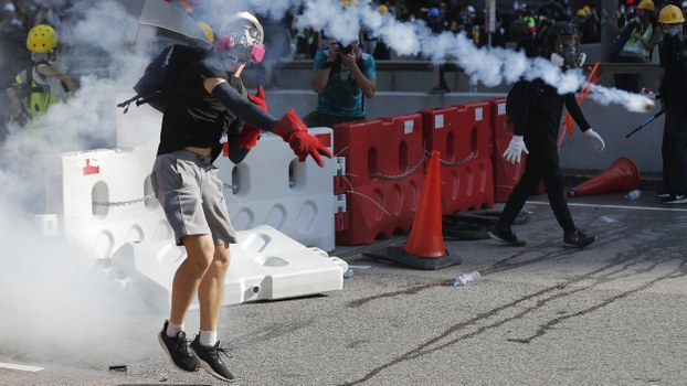 A protester throws back a tear gas canister in Hong Kong, Aug. 5, 2019.