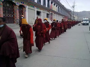 In this undated photo, sent by a Yushu resident, monks take part in a memorial for quake victims while escorted by police.