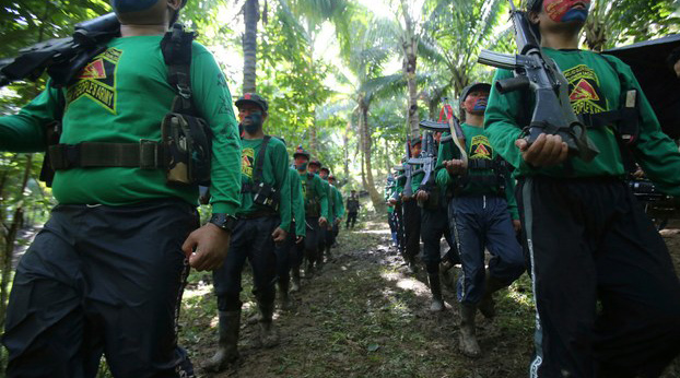 Guerrillas of the New People's Army, the military wing of the Communist Party of the Philippines, march at their encampment in the Sierra Madre mountains, southeast of Manila, Nov. 23, 2016.