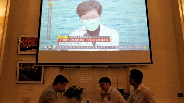 Friends have a drink as a projection is shown of a live press conference held by Chief Executive Carrie Lam, wearing a face mask as a precautionary measure against the COVID-19 coronavirus, in Hong Kong, March 23, 2020.