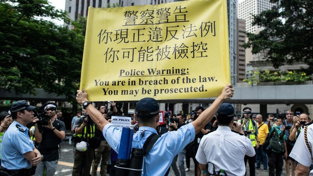 A police officer displays a warning banner during a flash mob rally to show support for pro-democracy protesters in the Central district in Hong Kong, Oct. 11, 2019.