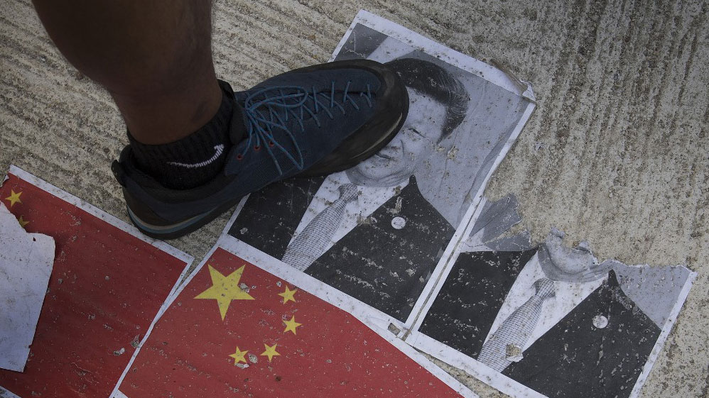 Protesters walk on an image of Chinese President Xi Jinping in the Causeway Bay area in Hong Kong, Oct. 1, 2019.