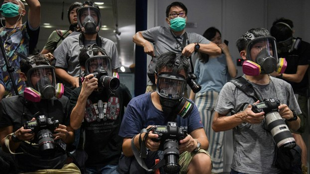 Photojournalists wearing protective masks attend a police press conference in Hong Kong Oct. 8, 2019.