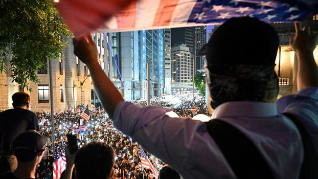 A man waves a US national flag as protesters attend a rally in Hong Kong, calling on US politicians to pass a bill that could alter Washington's relationship with the trading hub, Oct. 14, 2019