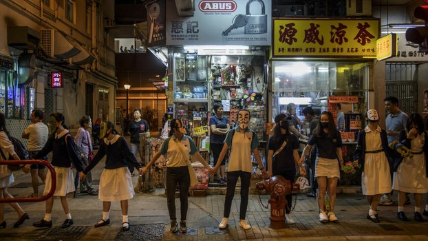 Masked students and protesters gather to form a human chain along a street in Hong Kong, Oct. 18, 2019.