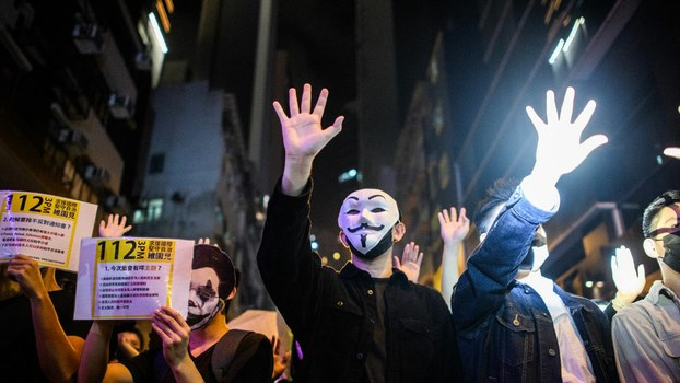 Revelers shout slogans at a line of police shining bright torches as they block entry to the Lan Kwai Fong area in Hong Kong, where democracy activists donned Halloween masks lampooning the city's pro-Beijing leaders Oct. 31, 2019.