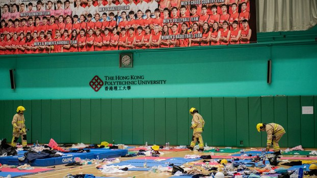 A safety team looks through a gymnasium used by protesters to sleep for dangerous explosives and chemicals at the Hong Kong Polytechnic University, Nov. 28, 2019.