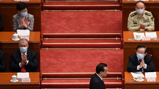 Hong Kong Chief Executive Carrie Lam (top L) and former Macau chief executive Edmund Ho (bottom L) applaud as Chinese Premier Li Keqiang returns to his seat after delivering his speech at the National People's Congress in Beijing, May 22, 2020.