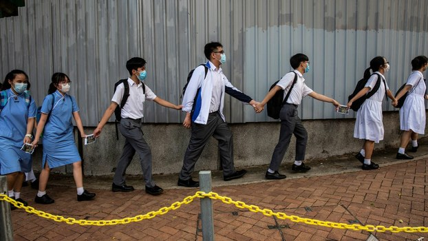 School students hold hands to form a human chain during a pro-democracy protests near their school in Hong Kong, June 12, 2020.