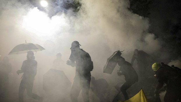 Protesters react to tear gas canister during clashes with police at the Chinese University of Hong Kong (CUHK) in Hong Kong, Nov. 12, 2019.