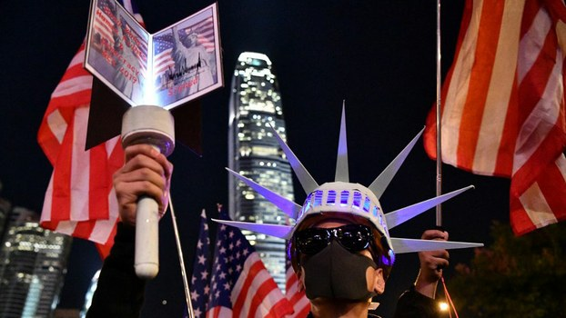 A participant holds a torch and wears headgear modeled after the Statue of Liberty as people assemble for a gathering of thanks at Edinburgh Place in Hong Kong's Central district Nov. 28, 2019.