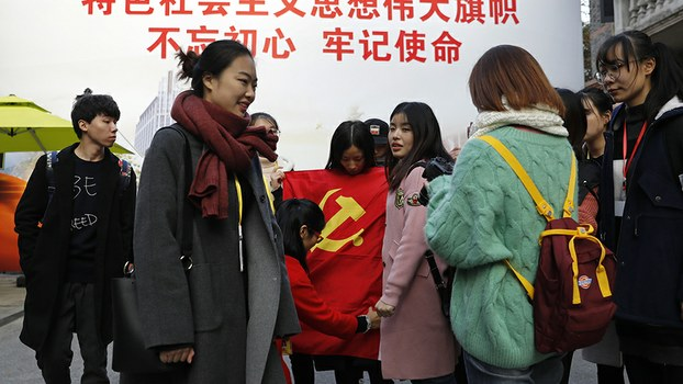 A group of university students fold a Communist Party flag after taking a photograph in front of a giant propaganda billboard in Shanghai, Nov. 19, 2017.