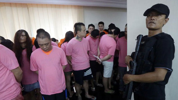 An Indonesian police officer in Jakarta guards Taiwanese and Chinese citizens who were arrested for alleged involvement in a cyber fraud ring, July 31, 2017.