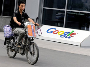 A man riding a motorcycle past the logo of Google's China headquarters in Beijing, June 30, 2010.