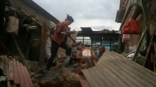 Residents gather belongings from a damaged farmhouse in the northeastern Chinese province of Jilin after a 5.7-magnitude earthquake rocked the city of Songyuan early on May 28.