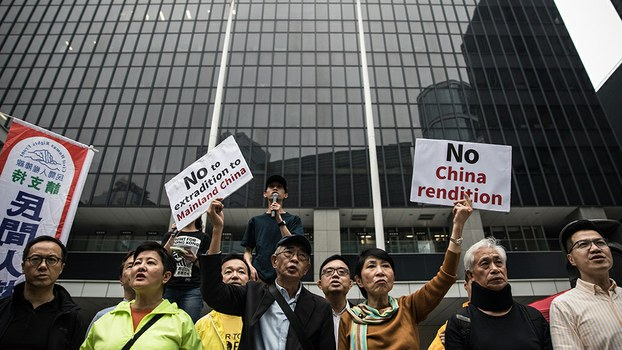 Protesters display placards rejecting plans to allow extraditions to the Chinese mainland outside government headquarters during a rally in Hong Kong, March 31, 2019.