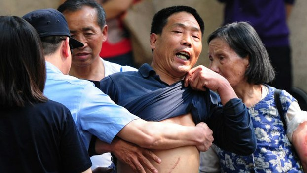 A Chinese petitioner protesting about a land grab issue is detained by police outside a hospital in Beijing, in 2012 file photo.