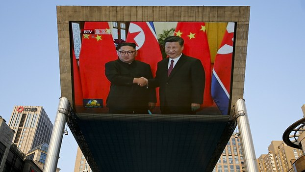 An outdoor television screen in Beijing shows North Korean leader Kim Jong Un and Chinese President Xi Jinping shaking hands, June 19, 2018.