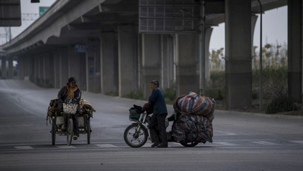 Two migrant workers with their tricycle under an elevated road in the suburbs of Shanghai, April 5, 2017.