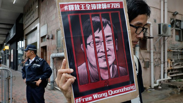 A supporter of jailed Chinese human rights lawyer Wang Quanzhang displyas his image at China's liason office in Hong Kong, July 13, 2018.